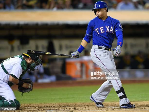 Catcher Geovany Soto of the Oakland Athletics gets hit in the head with the back swing of Leonys Martin of the Texas Rangers in the top of the third...