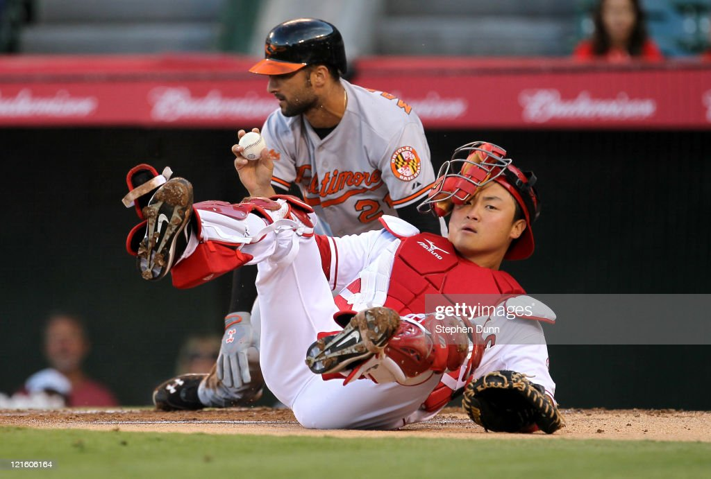 Catcher Hank Conger of the Los Angeles Angels of Anaheim shows the ball after tagging out Nick Markakis of the Baltimore Orioles at home plate in the...