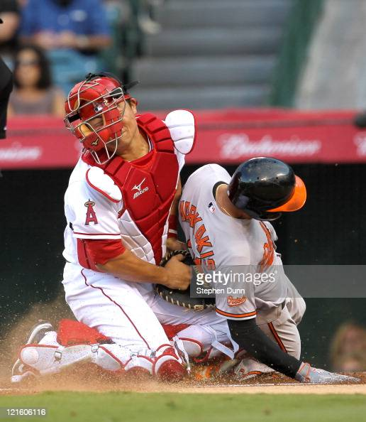 Catcher Hank Conger of the Los Angeles Angels of Anaheim tags out Nick Markakis of the Baltimore Orioles at home plate in the first inning on August...