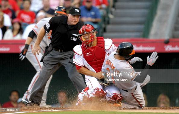 Catcher Hank Conger of the Los Angeles Angels of Anaheim tags out Nick Markakis of the Baltimore Orioles as home plate umpire Dana DeMuth watches in...