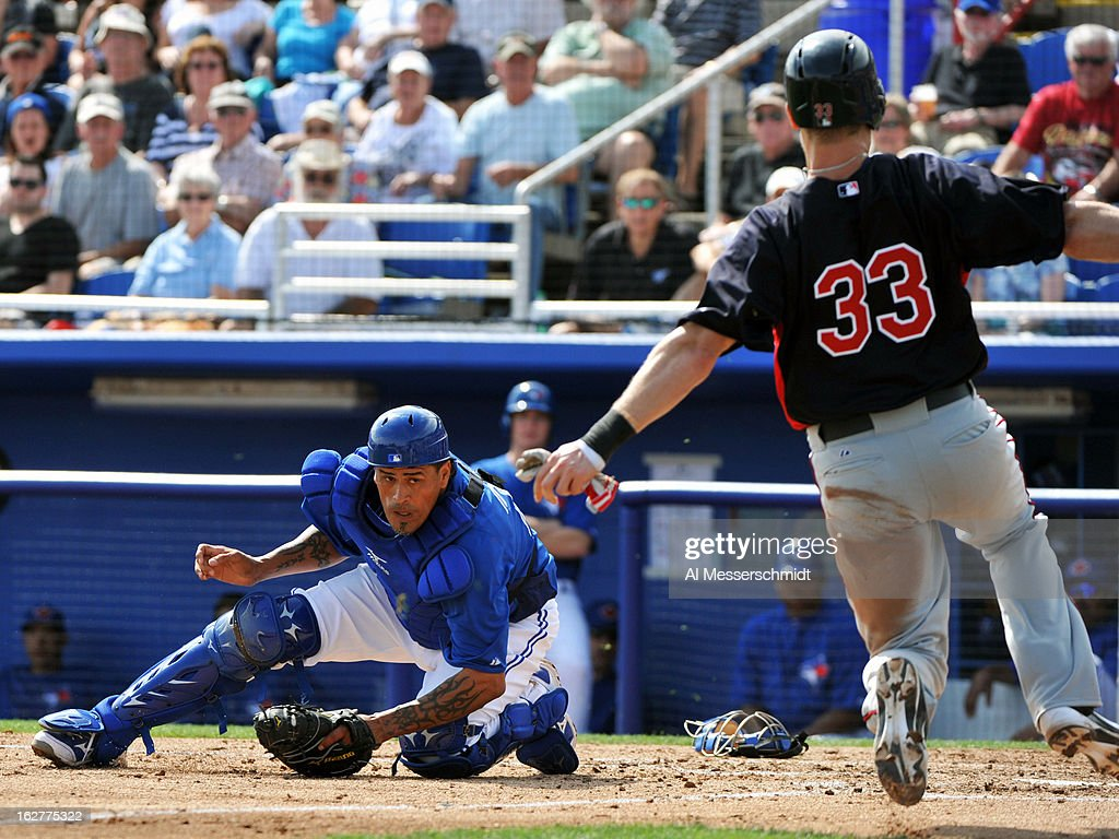 Catcher <a gi-track='captionPersonalityLinkClicked' href=/galleries/search?phrase=Henry+Blanco&family=editorial&specificpeople=211366 ng-click='$event.stopPropagation()'>Henry Blanco</a> #22 of the Toronto Blue Jays sets to tag sliding infielder <a gi-track='captionPersonalityLinkClicked' href=/galleries/search?phrase=Justin+Morneau&family=editorial&specificpeople=211556 ng-click='$event.stopPropagation()'>Justin Morneau</a> #33 of the Minnesota Twins February 26, 2013 at the Florida Auto Exchange Stadium in Dunedin, Florida.