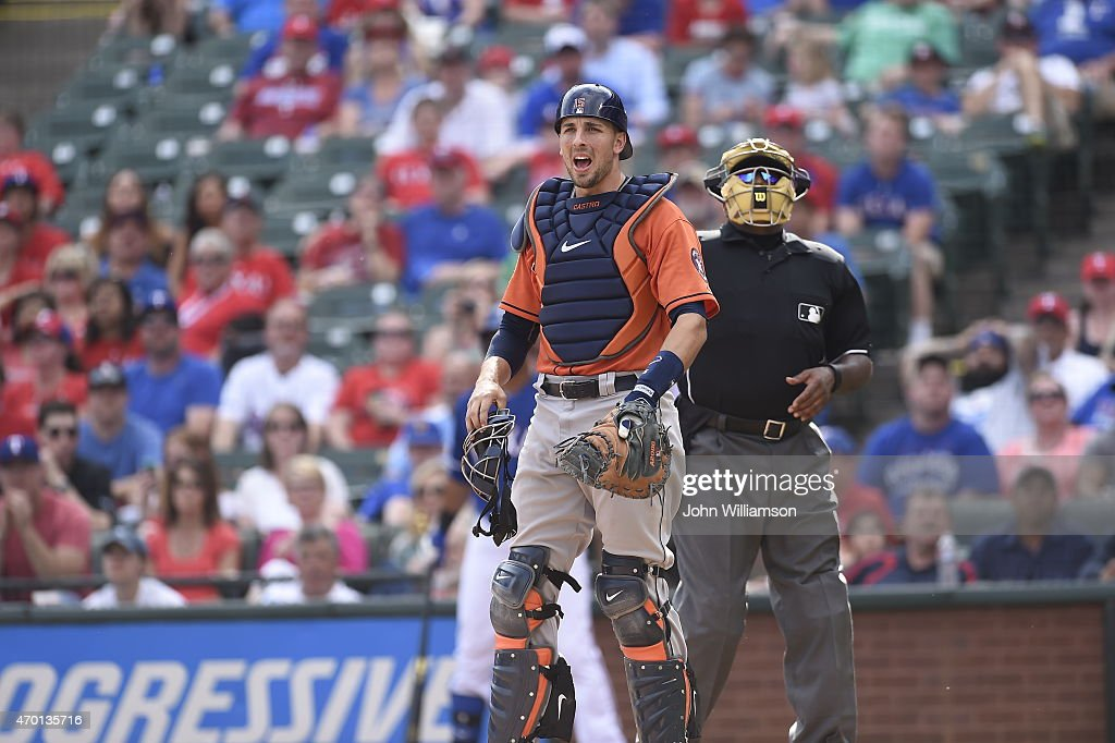 Catcher Jason Castro of the Houston Astros reacts to the play on a foul fly ball as home plate umpire Laz Diaz looks on in the game against the Texas...