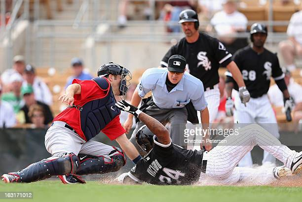 Catcher Joe Mauer of Team USA tags out Dayan Viciedo of the Chicago White Sox as he attempts to score a run during the spring training game at...