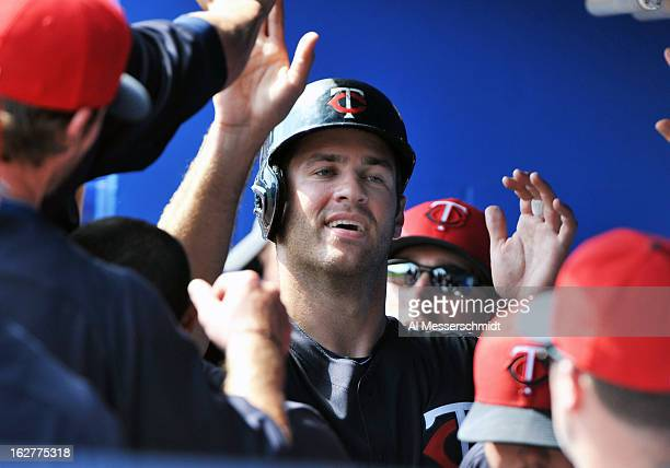 Catcher Joe Mauer of the Minnesota Twins celebrates after scoring a run against the Toronto Blue Jays February 26 2013 at the Florida Auto Exchange...