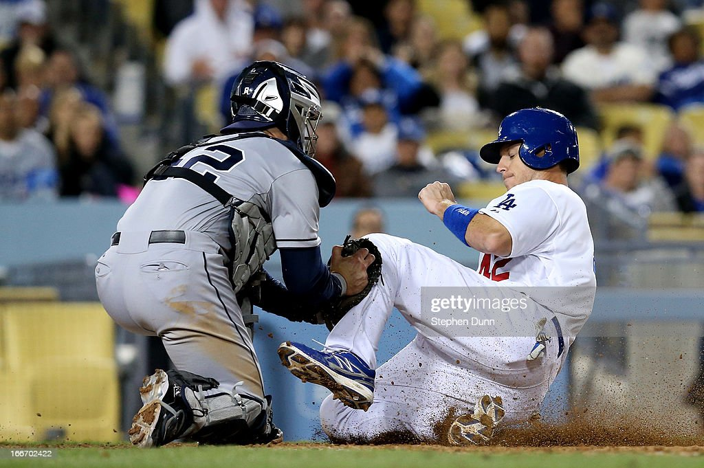 Catcher John Baker of the San Diego Padres tags out A.J. Ellis of the Los Angeles Dodgers as Ellis tries to score on a groundout to end the eighth inning at Dodger Stadium on April 15, 2013 in Los Angeles, California. All uniformed team members are wearing jersey number 42 in honor of Jackie Robinson Day.