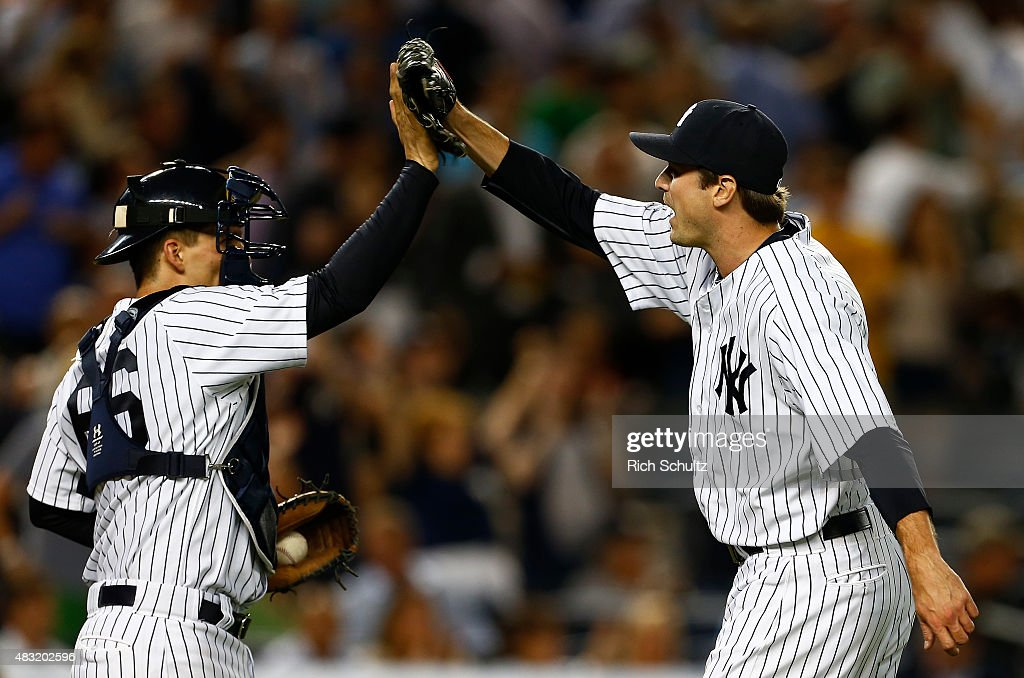 Catcher John Ryan Murphy #66 high fives pitcher Andrew Miller #48 of the New York Yankees after the final out in the ninth inning against the Boston Red Sox during a MLB baseball game at Yankee Stadium on August 6, 2015 in the Bronx borough of New York City. The Yankees defeated the Red Sox 2-1.