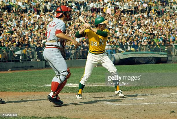 Catcher Johnny Bench of the Cincinnati Reds stands behind Gene Tenace of the Oakland Athletics getting his swing ready during the World Series at the...