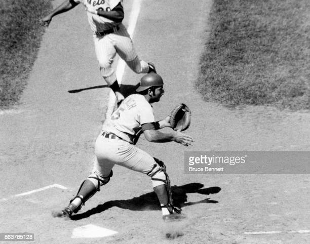 Catcher Johnny Bench of the Cincinnati Reds waits for the throw as Tommie Agee of the New York Mets gets ready to slide during an MLB game circa 1970...