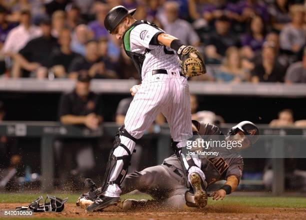 Catcher Jonathan Lucroy of the Colorado Rockies forces out Daniel Descalso of the Arizona Diamondbacks at home plate in the sixth inning at Coors...