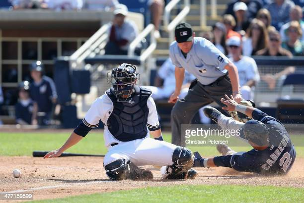 Catcher Jonathan Lucroy of the Milwaukee Brewers is unable to tag out Everth Cabrera of the San Diego Padres as he slides into home plate to score a...