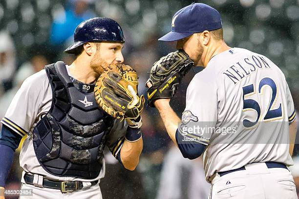 Catcher Jonathan Lucroy of the Milwaukee Brewers talks with starting pitcher Jimmy Nelson of the Milwaukee Brewers during the third inning against...