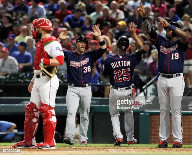 Catcher Jonathan Lucroy of the Texas Rangers looks on as Chris Gimenez Byron Buxton and Kennys Vargas of the Minnesota Twins celebrate scoring on an...