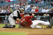 Catcher Jordan Pacheco of the Colorado Rockies tags out Martin Prado of the Arizona Diamondbacks as he attempts to score a run during the first...