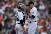 Catcher Jordan Pacheco talks with relief pitcher Matt Belisle of the Colorado Rockies as he works against the Philadelphia Phillies at Coors Field on...