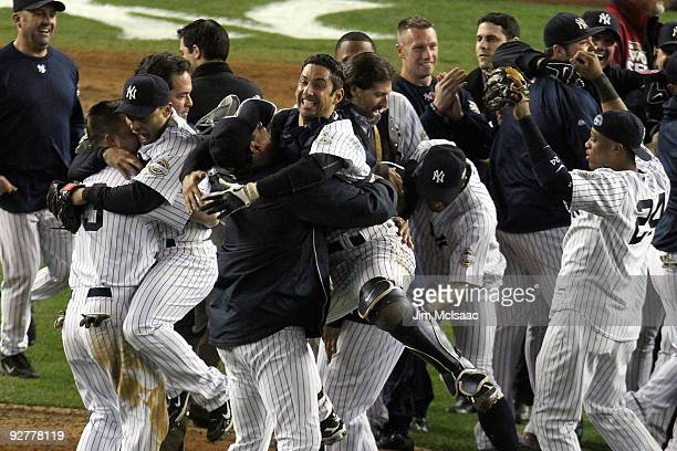 Catcher Jorge Posada of the New York Yankees celebrates with his teammates on the field after their 73 win against the Philadelphia Phillies in Game...