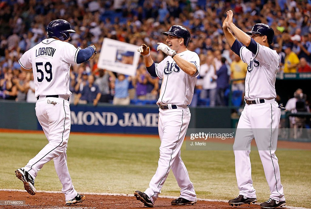 Catcher Jose Lobaton #59 of the Tampa Bay Rays is congratulated by Matt Joyce #20 and Kelly Johnson #2 after this second inning three run home run against the New York Yankees at Tropicana Field on August 23, 2013 in St. Petersburg, Florida.