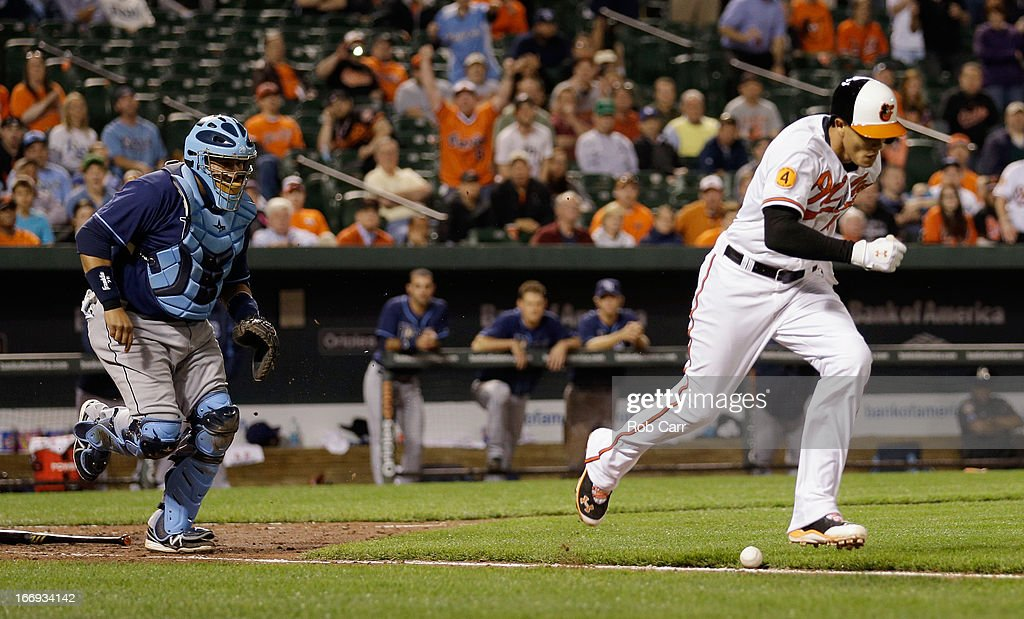 Catcher Jose Molina #28 of the Tampa Bay Rays goes after the ball as Manny Machado #13 of the Baltimore Orioles lays down a bunt and is safe at first base during the tenth inning of the Orioles 10-6 win at Oriole Park at Camden Yards on April 18, 2013 in Baltimore, Maryland.