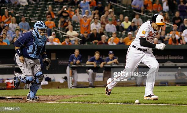 Catcher Jose Molina of the Tampa Bay Rays goes after the ball as Manny Machado of the Baltimore Orioles lays down a bunt and is safe at first base...