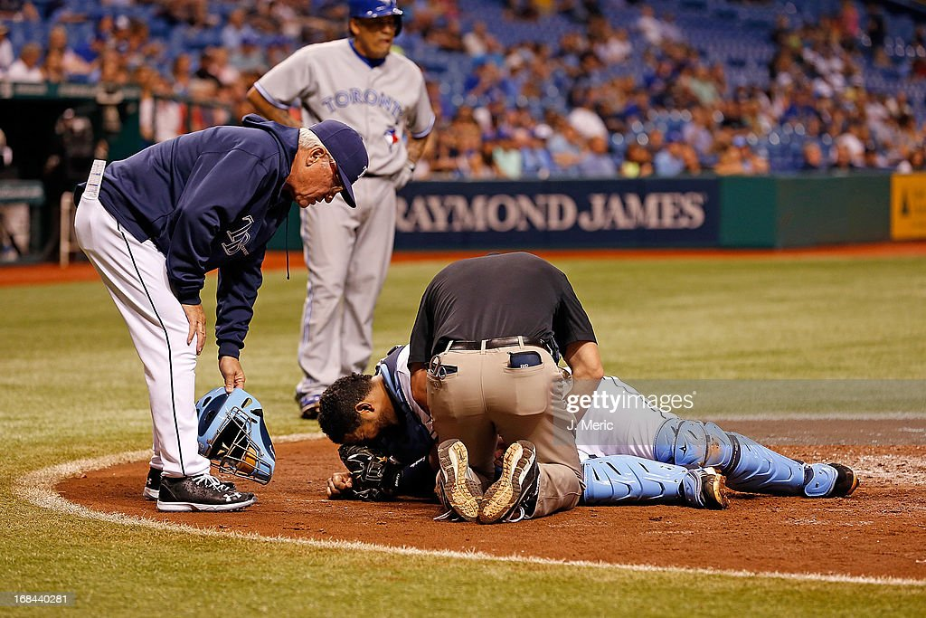 Catcher <a gi-track='captionPersonalityLinkClicked' href=/galleries/search?phrase=Jose+Molina&family=editorial&specificpeople=206365 ng-click='$event.stopPropagation()'>Jose Molina</a> #28 of the Tampa Bay Rays is injured as manager <a gi-track='captionPersonalityLinkClicked' href=/galleries/search?phrase=Joe+Maddon&family=editorial&specificpeople=568433 ng-click='$event.stopPropagation()'>Joe Maddon</a> #70 looks on during the game against the Toronto Blue Jays at Tropicana Field on May 9, 2013 in St. Petersburg, Florida.