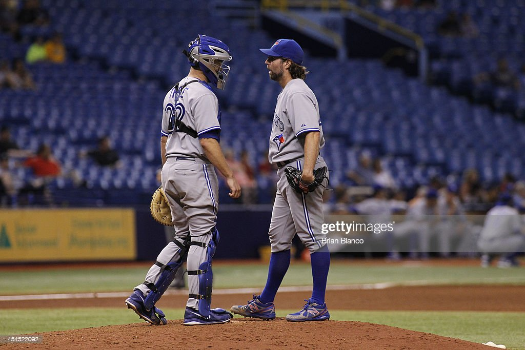 Catcher Josh Thole #22 of the Toronto Blue Jays comes out to the mound to speak to pitcher R.A. Dickey #43 after Dickey walked Yunel Escobar of the Tampa Bay Rays during the sixth inning of a game on September 2, 2014 at Tropicana Field in St. Petersburg, Florida.