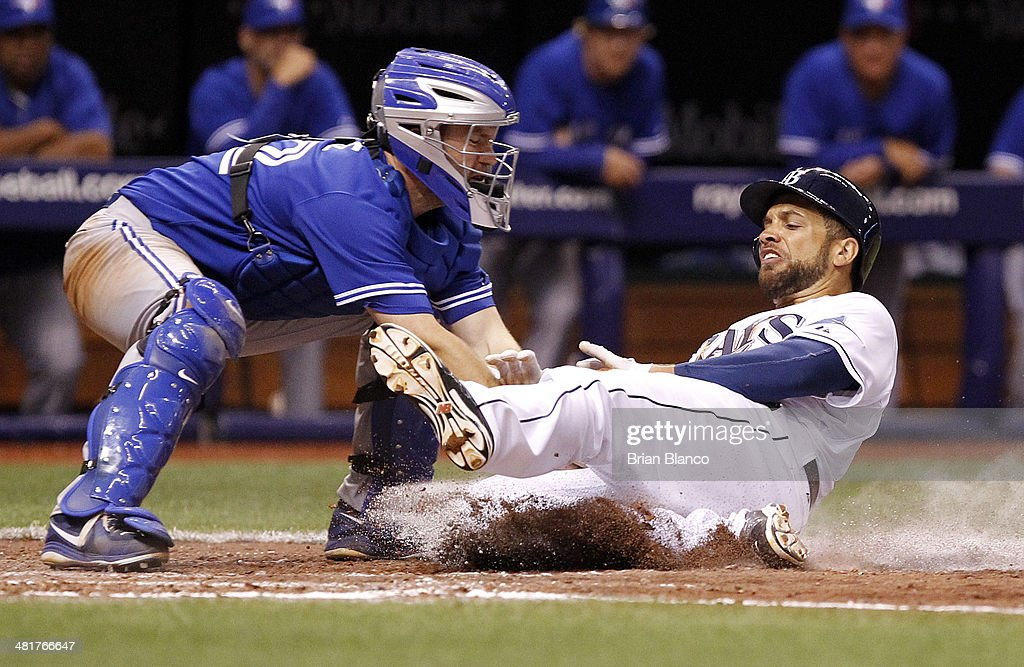 Catcher <a gi-track='captionPersonalityLinkClicked' href=/galleries/search?phrase=Josh+Thole&family=editorial&specificpeople=5741573 ng-click='$event.stopPropagation()'>Josh Thole</a> #22 of the Toronto Blue Jays gets the out at home plate on <a gi-track='captionPersonalityLinkClicked' href=/galleries/search?phrase=James+Loney&family=editorial&specificpeople=636293 ng-click='$event.stopPropagation()'>James Loney</a> #21 of the Tampa Bay Rays during the seventh inning of a game on Opening Day on March 31, 2014 at Tropicana Field in St. Petersburg, Florida.