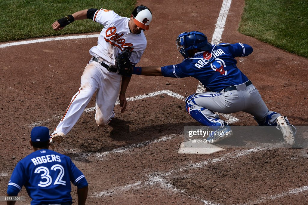 Catcher J.P. Arencibia #9 of the Toronto Blue Jays tags out base runner Manny Machado #13 of the Baltimore Orioles in the tenth inning at Oriole Park at Camden Yards on April 24, 2013 in Baltimore, Maryland. The Toronto Blue Jays won, 6-5.