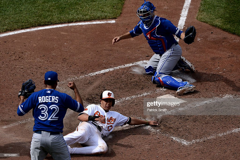 Catcher J.P. Arencibia #9 of the Toronto Blue Jays tags out base runner Manny Machado #13 of the Baltimore Orioles in the tenth inning as pitcher Esmil Rogers #32 of the Toronto Blue Jays celebrates at Oriole Park at Camden Yards on April 24, 2013 in Baltimore, Maryland. The Toronto Blue Jays won, 6-5.