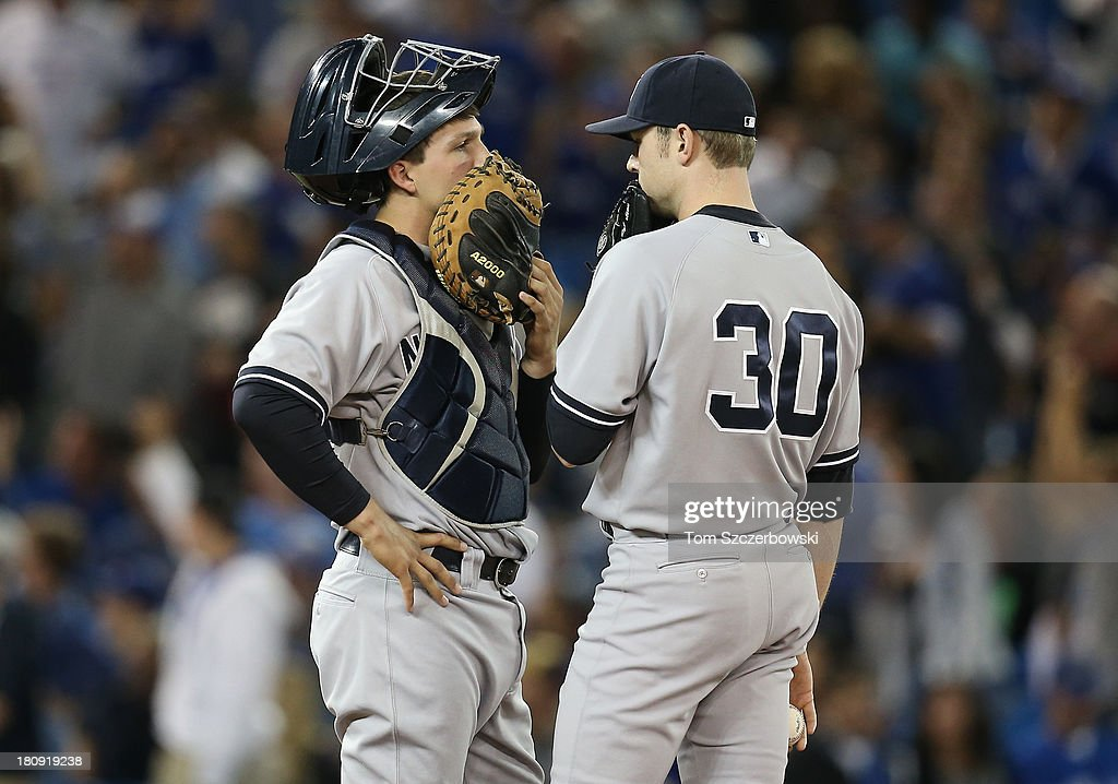 Catcher J.R. Murphy #66 of the New York Yankees talks to David Robertson #30 on the mound during MLB game action against the Toronto Blue Jays on September 17, 2013 at Rogers Centre in Toronto, Ontario, Canada.