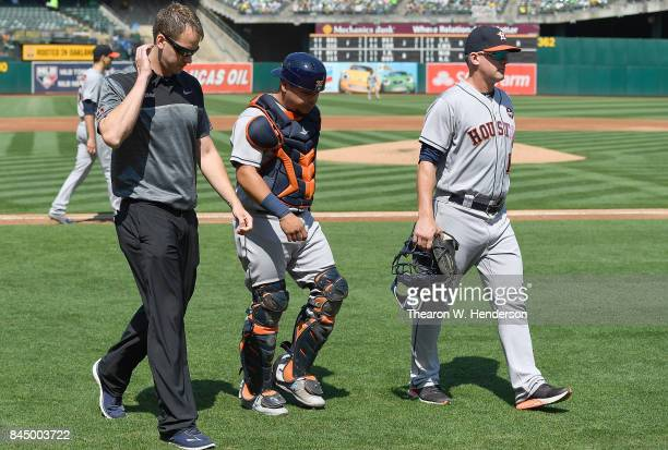 Catcher Juan Centeno of the Houston Astros walks off the field with trainer Jeremiah Randall and head coach AJ Hinch after Centeno was hit in the...