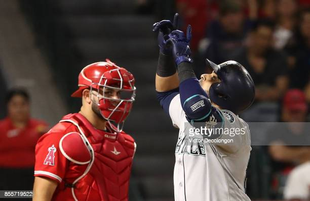 Catcher Juan Graterol of the Los Angeles Angels of Anaheim looks on as Nelson Cruz of the Seattle Mariners points to the sky after crossing homeplate...