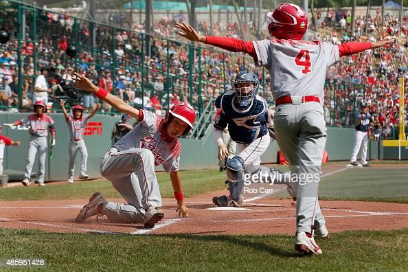 Catcher Kaden Peifer of the MidAtlantic team from Red Land Little League of Lewisberry Pennsylvania looks on as Shingo Tomita of team Japan scores a...