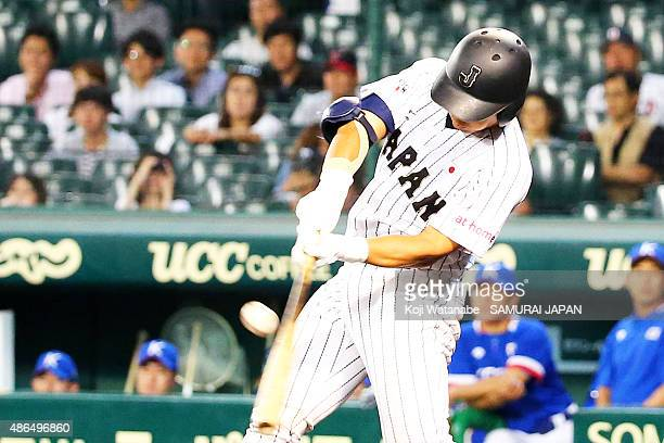 Catcher Kengo Horiuchi of Japan hits a RBI single in the bottom half of the fifth inning the game between Australia and Japan in the super round game...