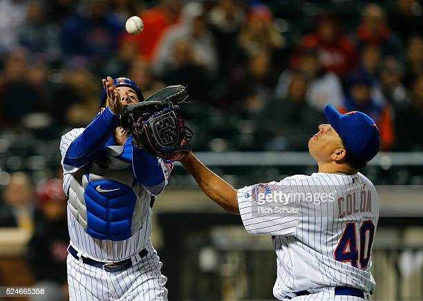 Catcher Kevin Plawecki of the New York Mets collides with pitcher Bartolo Colon before making a catch on a popup hit by Zack Cozart of the Cincinnati...