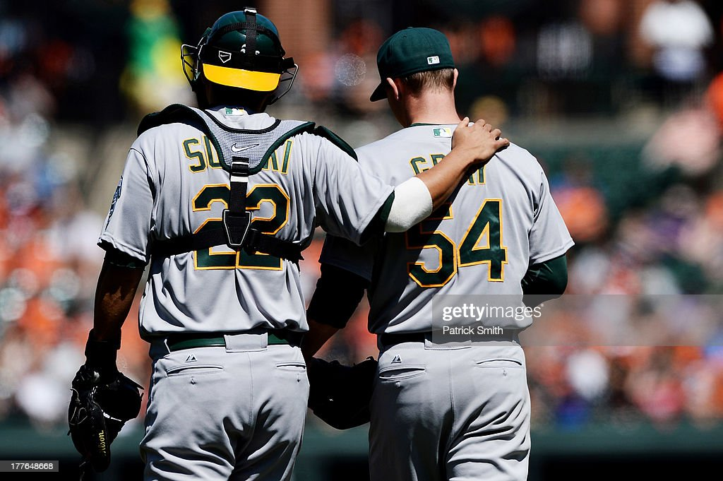 Catcher <a gi-track='captionPersonalityLinkClicked' href=/galleries/search?phrase=Kurt+Suzuki&family=editorial&specificpeople=682702 ng-click='$event.stopPropagation()'>Kurt Suzuki</a> #22 of the Oakland Athletics comforts teammate pitcher <a gi-track='captionPersonalityLinkClicked' href=/galleries/search?phrase=Sonny+Gray&family=editorial&specificpeople=8046451 ng-click='$event.stopPropagation()'>Sonny Gray</a> #54 after giving up a hit and run to the Baltimore Orioles in the second inning at Oriole Park at Camden Yards on August 25, 2013 in Baltimore, Maryland.