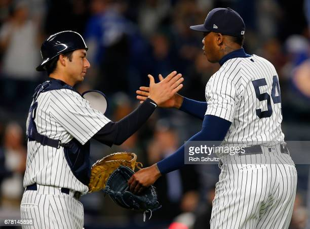 Catcher Kyle Higashioka and closer Aroldis Chapman of the New York Yankees congratulate each other after defeating the Toronto Blue Jays 86 in a game...