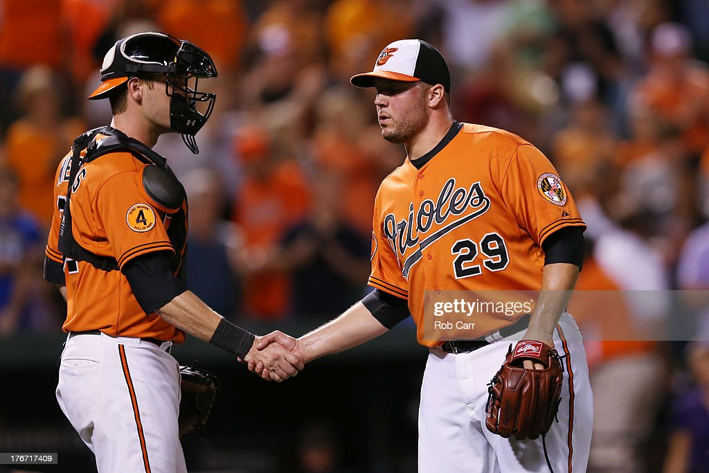 Catcher <a gi-track='captionPersonalityLinkClicked' href=/galleries/search?phrase=Matt+Wieters&family=editorial&specificpeople=4498276 ng-click='$event.stopPropagation()'>Matt Wieters</a> #32 and pitcher Tommy Hunter #29 of the Baltimore Orioles celebrate following the Orioles 8-4 win over the Colorado Rockies at Oriole Park at Camden Yards on August 17, 2013 in Baltimore, Maryland.