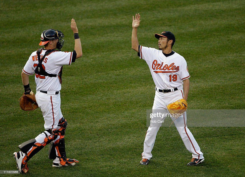 Catcher Matt Wieters #32 of the Baltimore Orioles and reliever Koji Uehara #19 celebrate after the Orioles defeated the Detroit Tigers 5-1 during opening day at Oriole Park at Camden Yards on April 4, 2011 in Baltimore, Maryland.