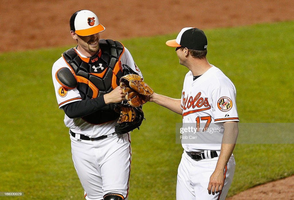 Catcher Matt Wieters #32 of the Baltimore Orioles is congratulated by pitcher Brian Matusz #17 after Wieters caught a pop up for the third out of the eighth inning against the Kansas City Royals at Oriole Park at Camden Yards on May 8, 2013 in Baltimore, Maryland. The Orioles won 5-3.