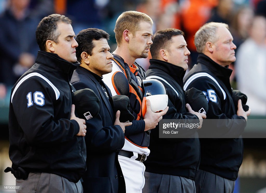 Catcher Matt Wieters #32 of the Baltimore Orioles stands with the umpires during the playing of the national anthem before the start of the Orioles and Toronto Blue Jays game at Oriole Park at Camden Yards on April 23, 2013 in Baltimore, Maryland.