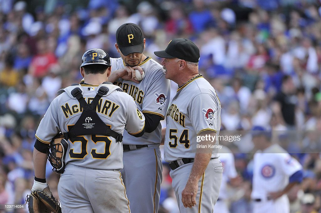 Catcher Michael McKenry #55 (L) of the Pittsburgh Pirates and pitching coach Ray Searage #54 (R) talk with pitcher Charlie Morton during the fifth inning against the Chicago Cubs at Wrigley Field on September 4, 2011 in Chicago, Illinois. The Cubs won 6-3.