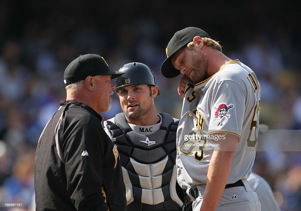 Catcher Michael McKenry #19 of the Pittsburgh Pirates looks on as pitching coach Ray Searage #54 has a word with pitcher Chris Leroux #63 in the seventh inning during the MLB game against the Los Angeles Dodgers at Dodger Stadium on April 7, 2013 in Los Angeles, California. The Dodgers defeated the Pirates 6-2.