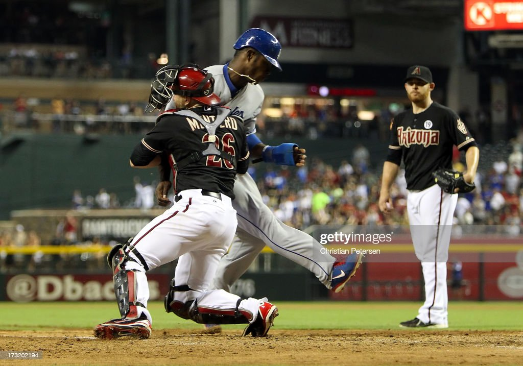 Catcher Miguel Montero of the Arizona Diamondbacks tags out Yasiel Puig of the Los Angeles Dodgers as he attempts to score a run as pitcher Ian...