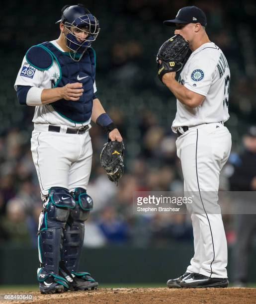 Catcher Mike Zunino left of the Seattle Mariners talks with reliever pitcher Dan Altavilla of the Seattle Mariners on the pitcher's mound during a...