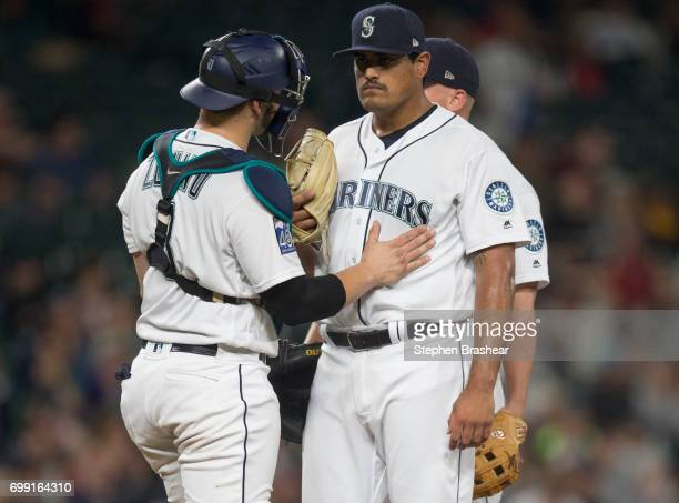 Catcher Mike Zunino of the Seattle Mariners and relief pitcher James Pazos of the Seattle Mariners meet at the pitcher's mound during a game against...