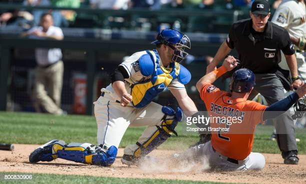 Catcher Mike Zunino of the Seattle Mariners is unable to tag out Alex Bregman of the Houston Astros on a hit by Josh Reddick of the Houston Astros...