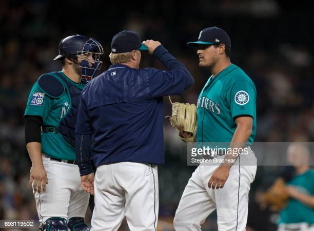 Catcher Mike Zunino of the Seattle Mariners pitching coach Mel Stottlemyre Jr and relief pitcher James Pazos of the Seattle Mariners meet at the...
