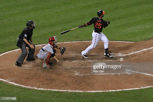 Catcher Ramon Hernandez of the Cincinnati Reds and umpire Gary Cederstrom look on as Derrek Lee of the Baltimore Orioles follows his walk off home...