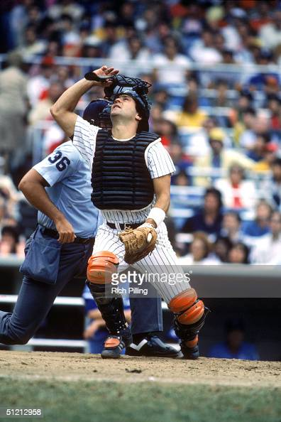 Catcher Rick Cerone of the New York Yankees removes his facemask as he follows a pop foul ball during a MLB season game circa August of 1983 at...