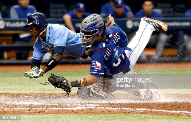 Catcher Robinson Chirinos of the Texas Rangers gets the out at home on Adeiny Hechavarria of the Tampa Bay Rays off of the fielder's choice by Jesus...