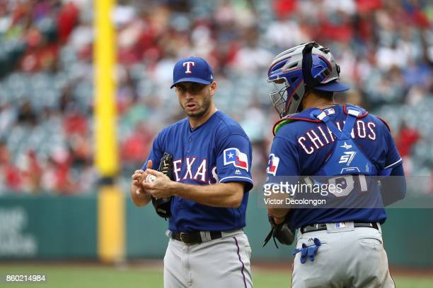 Catcher Robinson Chirinos of the Texas Rangers talks to pitcher Miguel Gonzalez in the infield grass during the fifth inning of the MLB game against...